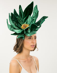 Woman wearing large emerald velvet flower fascinator with bead detailing