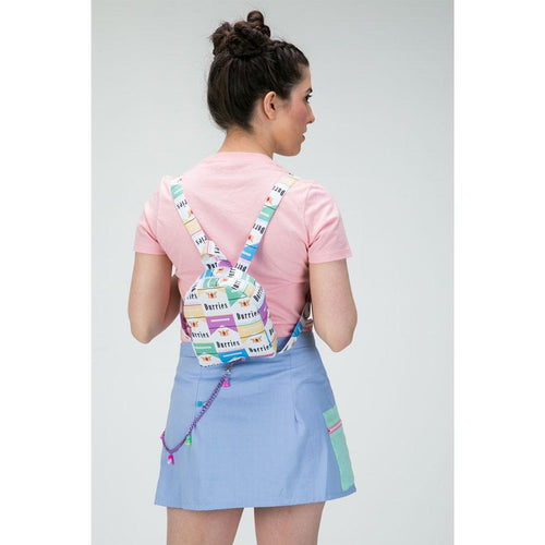 Back view of model wearing a mini backpack with pastel durries print