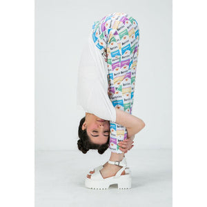 Model leaning over wears pants with pastel durries print