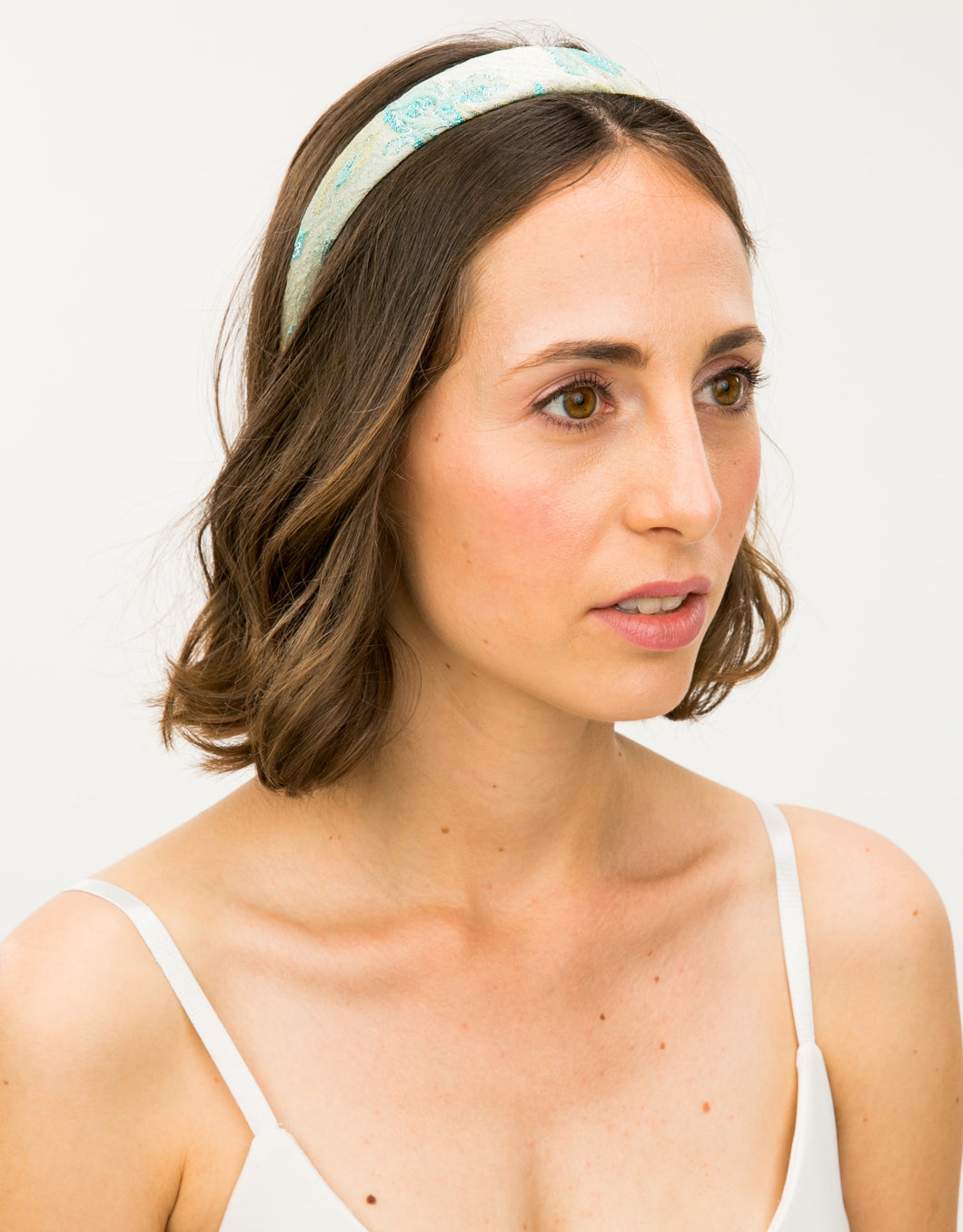Model wears wide blue and gold brocade headband