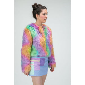Model standing in rainbow fur jacket with lolly decorations and purple skirt