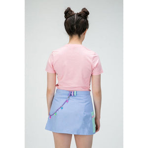 Back view of a woman wearing a pink t-shirt  tucked into an purple mini skirt with charm chain detail