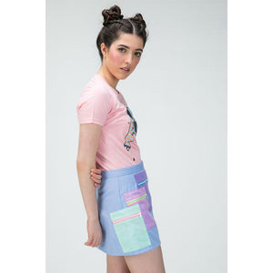 Side view of a woman wearing a pink t-shirt with an illustration, tucked into an purple mini skirt with layered contrast pockets