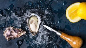 shucked oyster oyster knife and lemons on beautiful background with ice