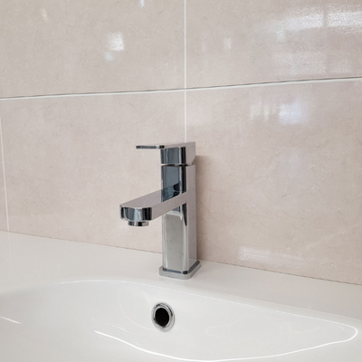 Tap and washbasin on the background of a wall made of Dumalock Monaco Beige Panels