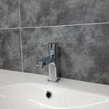 Tap and washbasin on the background of a wall made of Dumalock Light Concrete Panels