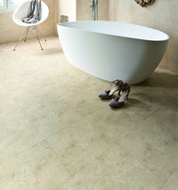 A bathtub on a floor made of TLC Loc Admiral Limestone Stone Tile Effect Flooring