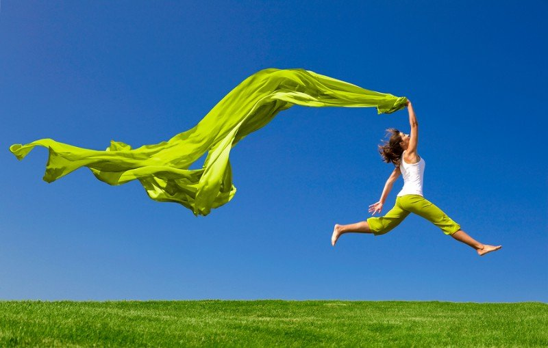 Beautiful young woman jumping on  a green meadow with a colored