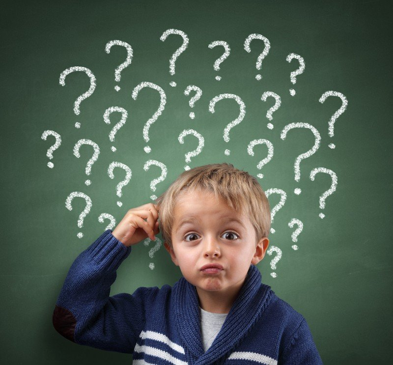 Child scratching head with question mark on blackboard concept f