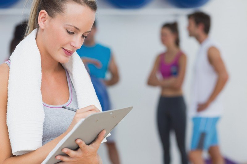Female trainer writing on clipboard with fitness class in backgr