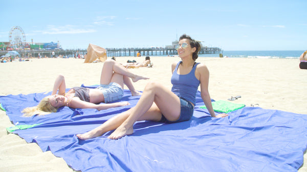 Girls laying on sand free beach blanket at the beach