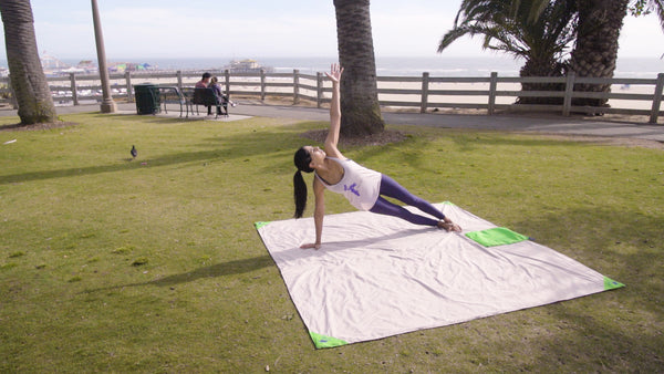 A young woman practicing yoga on the park by the beach with a BeachSheetz blanket
