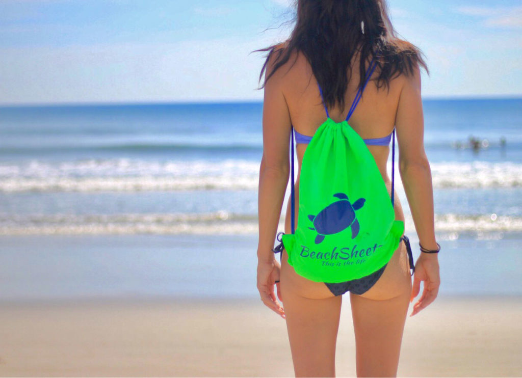 behind view of a girl looking at the ocean with a beachsheetz backpack on