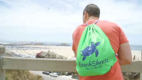 BeachSheetz backpack being worn by a young man overlooking the beach