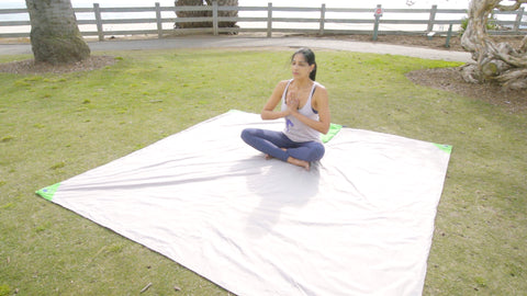 Woman meditating in the park while sitting on her beachsheetz beach blanket
