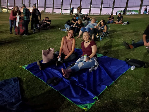 Two girls laying out on the BeachSheetz outdoor blanket at a concert