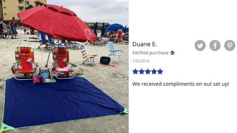 A couple showcasing their beach day set up using the beachsheetz blanket as a tarp area