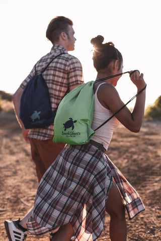 Couple hiking with their drawstring backpack blanket