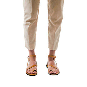 Model wearing Mara tan, handmade leather sandals with back strap and toe loop
