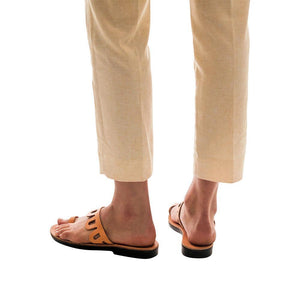 Model wearing Aja tan, handmade leather slide sandals with toe loop