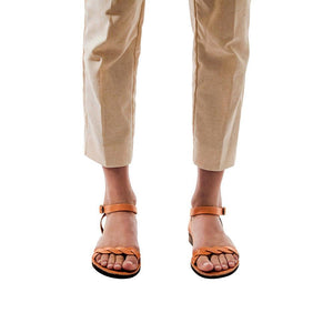 Model wearing Arden tan, handmade leather sandals with back strap