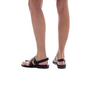 Model  wearing Benjamin black, handmade leather sandals with back strap and toe loop