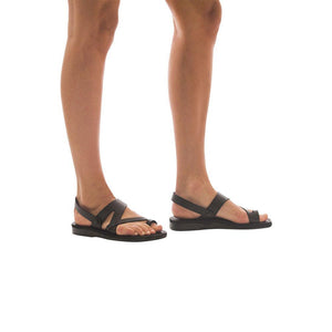 Model wearing Benjamin brown, handmade leather sandals with back strap and toe loop