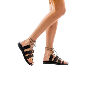 Model wearing brown, handmade leather sandals with back strap and toe loop
