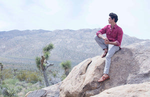 a male model sitting on a rock wearing Jerusalem sandals looking to distance