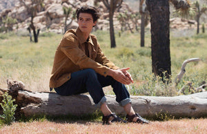 a male model sitting on a tree trunk wearing Jerusalem sandals