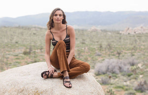 a female model sitting on a rock wearing Jerusalem sandals