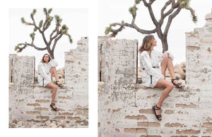 a female model sitting on a wall wearing Jerusalem sandals