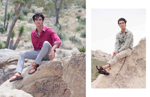 a male model sitting on a rock wearing Jerusalem sandals