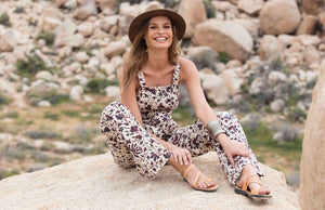 a female model sitting on a rock laughing and wearing Jerusalem sandals