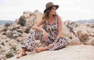 a female model with a hat sitting on a rock wearing Jerusalem sandals