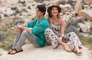 a male and female models sitting o a rock wearing Jerusalem sandals