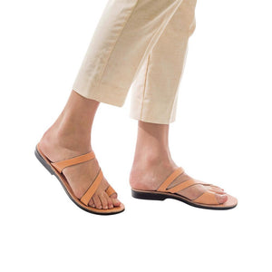Model wearing Noah tan, handmade leather slide sandals with toe loop