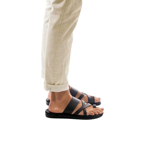 Model wearing The Good Shepherd black, handmade leather slide sandals with toe loop