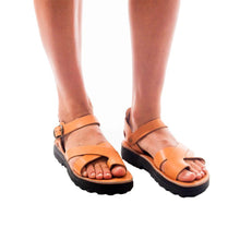 Load image into Gallery viewer, Model wearing Tovah tan, handmade leather sandals with back strap and toe loop