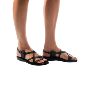 Model wearing Tzippora black, handmade leather sandals with back strap