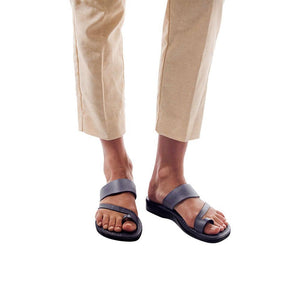 Model wearing Zohar gray, handmade leather slide sandals with toe loop
