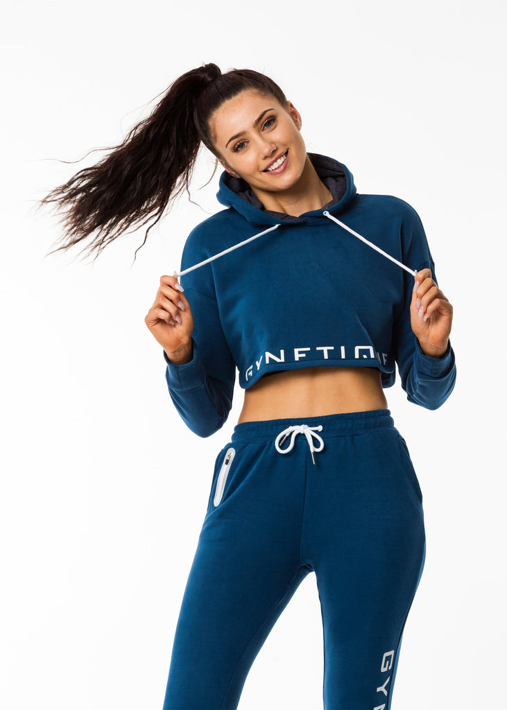 Gynetique gym clothes nz, women's cropped hoodie in blue colour, lined hood, white drawstring, half print logo design