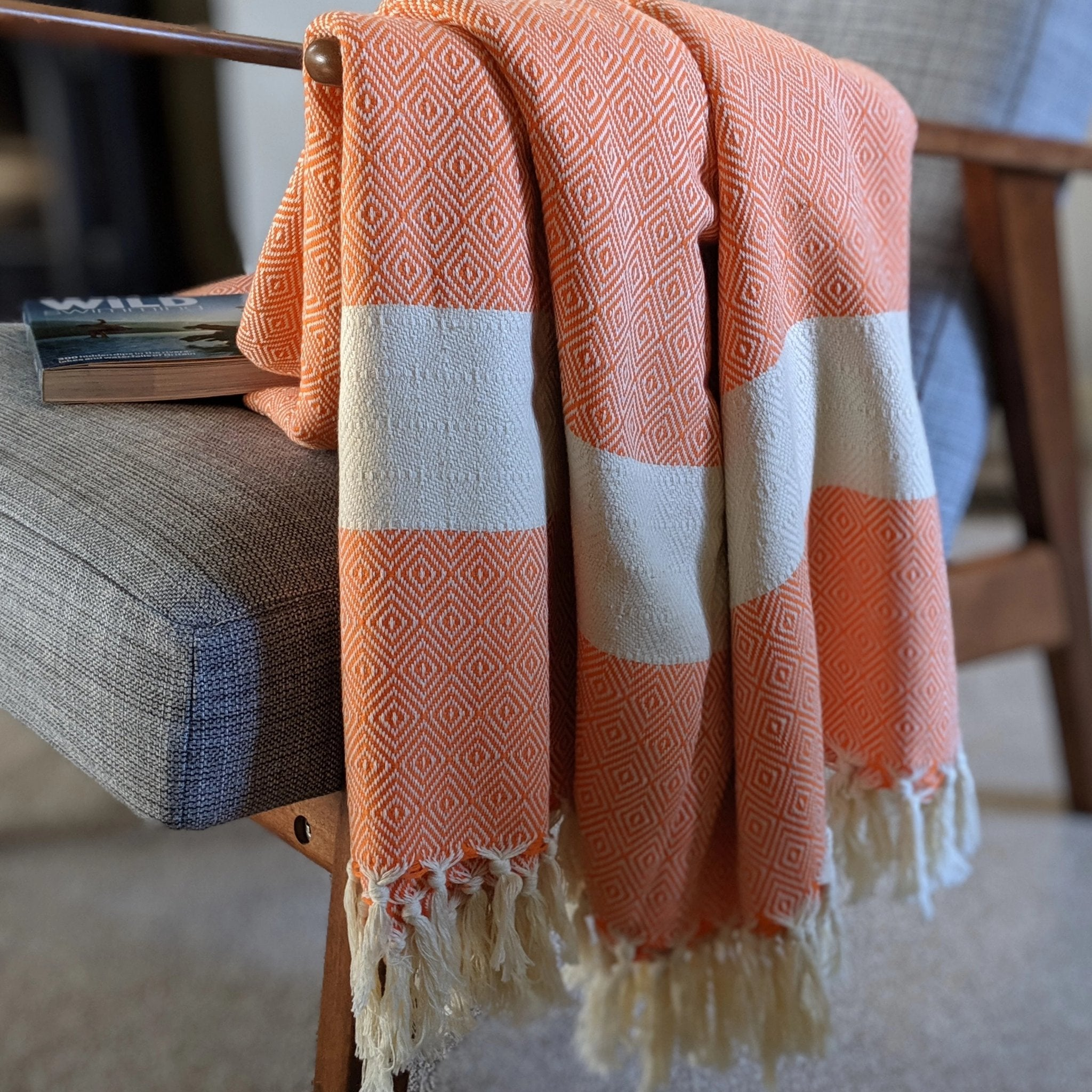 Orange colour organic cotton blanket draped over chair