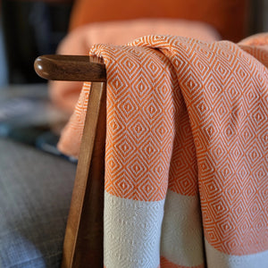 Organic cotton blanket draped over chair arm