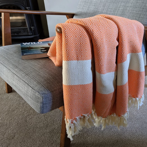 Organic cotton blanket draped over chair with wild swim book