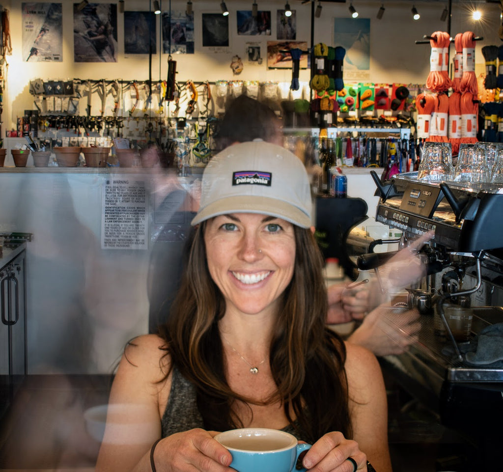 woman wearing a patagonia hat holding a coffee in the Neptune cafe