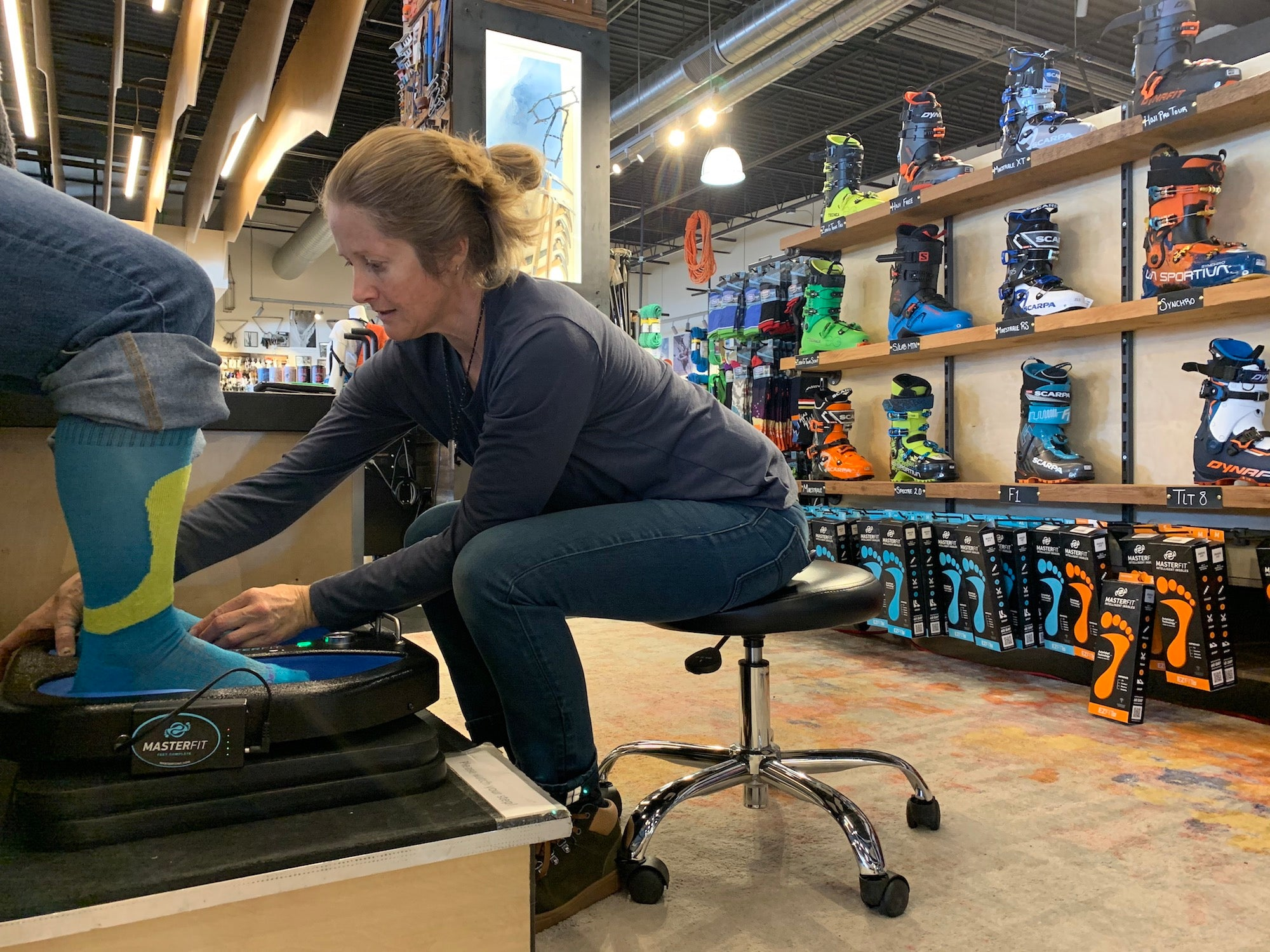 An image of one of our bootfitters molding custom footbeds for a customer. Our bootfitter is sitting on a rolling chair and has ski boots displayed behind her.