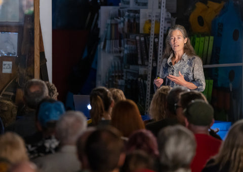 An image of Lynn Hill speaking to a crowd at her June 2019 presentation at Neptune Mountaineering
