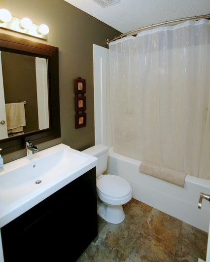 small dark bathroom with slate tile, curved shower rod, small shower/bathtub combination, semi-transparent shower curtain... 5 Steps to Make Your Small Shower Look Bigger Without Remodeling from Bathroom Bliss by Rotator Rod