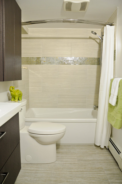 small beige bathroom with curved shower curtain rod, striped tile, green and white accents, dark cabinetry... 5 Steps to Make Your Small Shower Look Bigger Without Remodeling from Bathroom Bliss by Rotator Rod